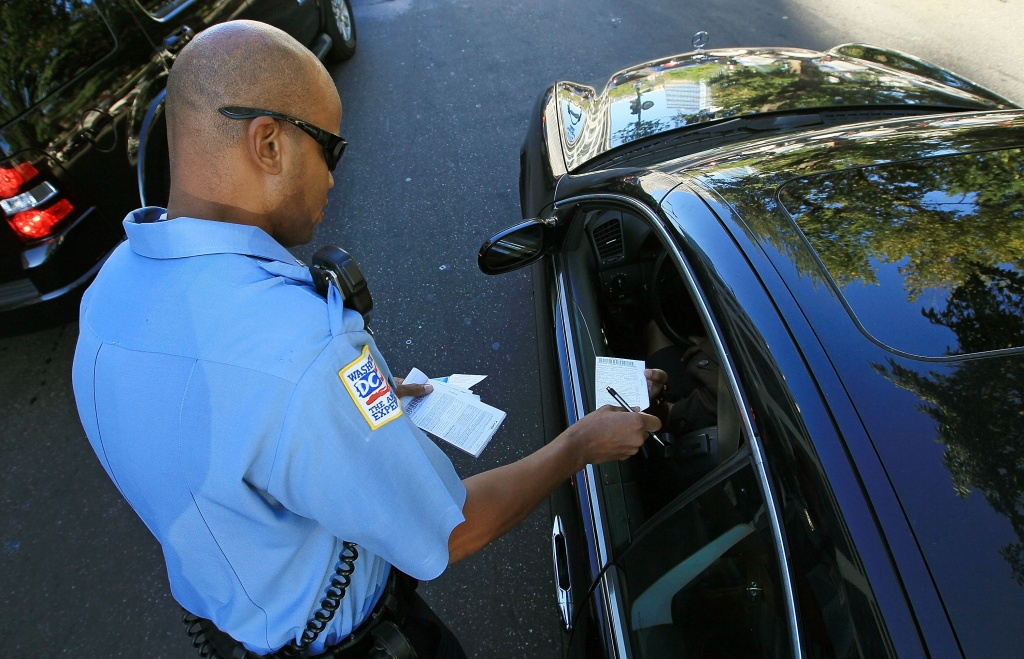 A police officer hands out a warning to motorist who was talking on his cell phone.