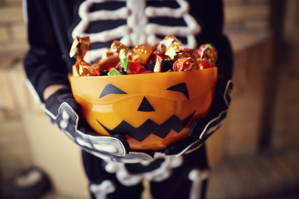 Child holds bowl of candy in skeleton costume.
