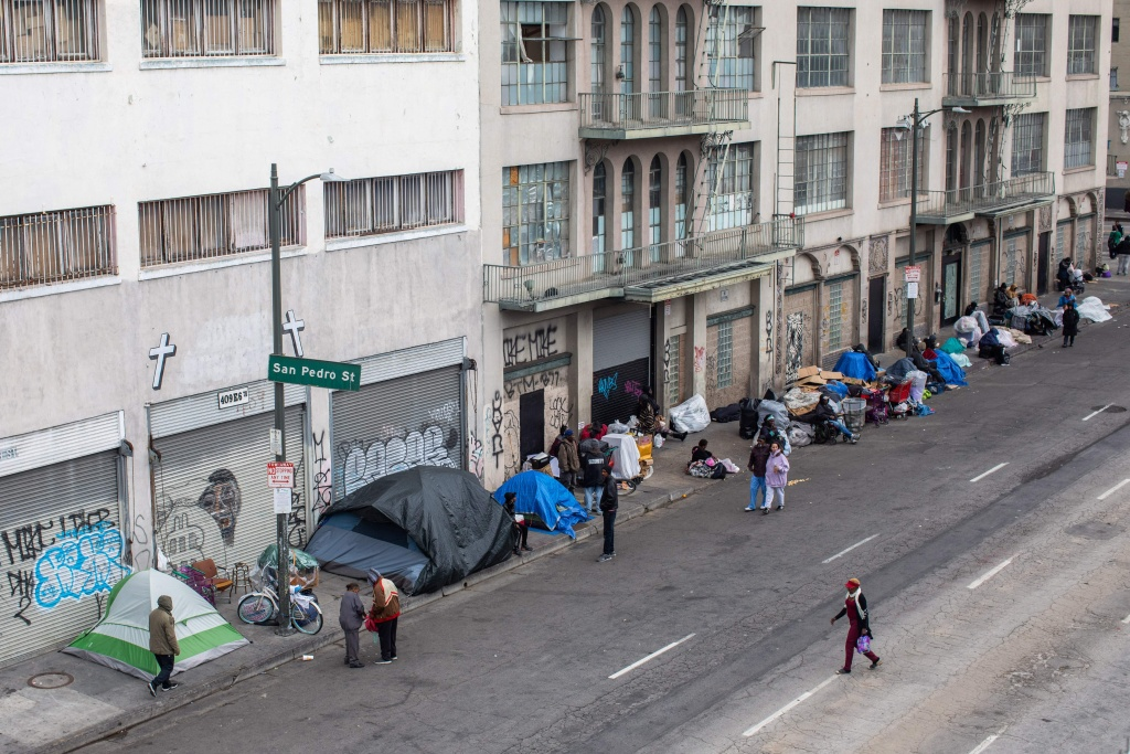 Homeless people make shelters on the sidewalk in front of the Midnight Mission at Skid Row in downtown Los Angeles, California on March 19, 2020.