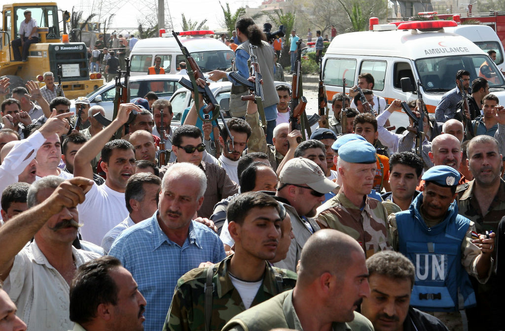 Syrian security forces raise their weapons in the air as Norwegian Major General Robert Mood, head of the UN observers mission in Syria, arrives to inspect the site of twin blasts in Damascus on May 10, 2012.