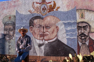 Mexican-American muralist Antonio Pazos stands by one of his giant murals 02 October in Tucson, Arizona.
