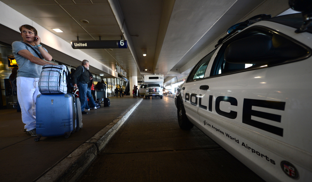 Kevin Aksacki who just arrived from Brazil makes a phone call next to a Police vehicle parked curbside at Los Angeles International Airport amid a heightened security alert on April 16, 2013.