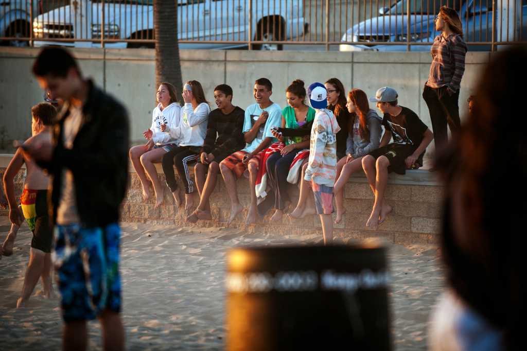 High school friends pose for a group picture at the Huntington Beach fire pits on Thursday evening, June 6. The South Coast Air Quality Management District says the fires release emissions that are harmful to the environment.