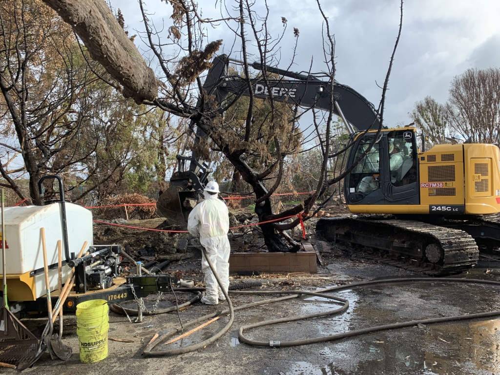 A worker sprays down debris before a claw truck picks it up at a home burned down in the Woolsey Fire in Malibu.
