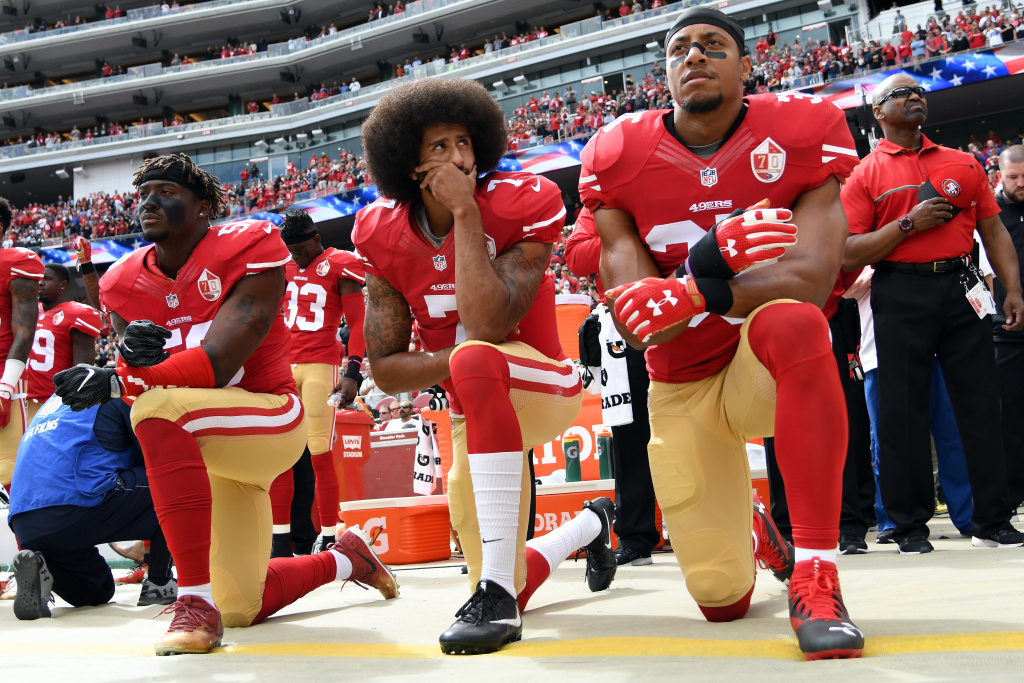 Eli Harold, Colin Kaepernick and Eric Reid of the San Francisco 49ers kneel on the sideline during the national anthem before a game against the Dallas Cowboys on October 2, 2016 in Santa Clara, California.