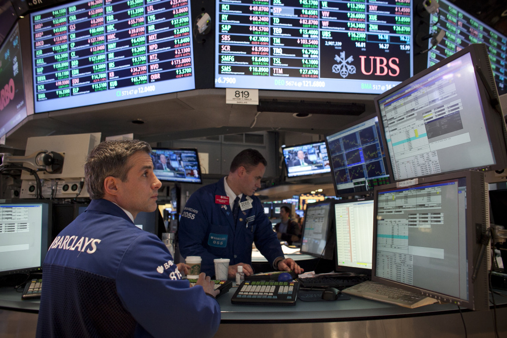 In this file photo, traders work on the floor of the New York Stock Exchange in New York City. The Dow tumbled more than 300 points by Monday afternoon amid reports of sluggish global growth.