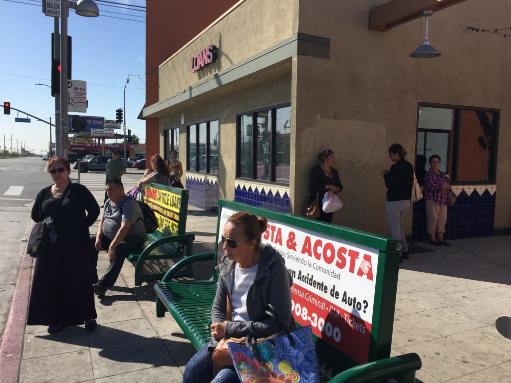 FILE: Passengers wait at a bus stop in Pacoima. Riders without smart phones don't have access to real-time arrival information. But plans to install electronic signs at the busiest stops will change that.