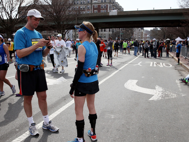 A runner using his cell phone after two bombs exploded at the Boston Marathon on Monday.