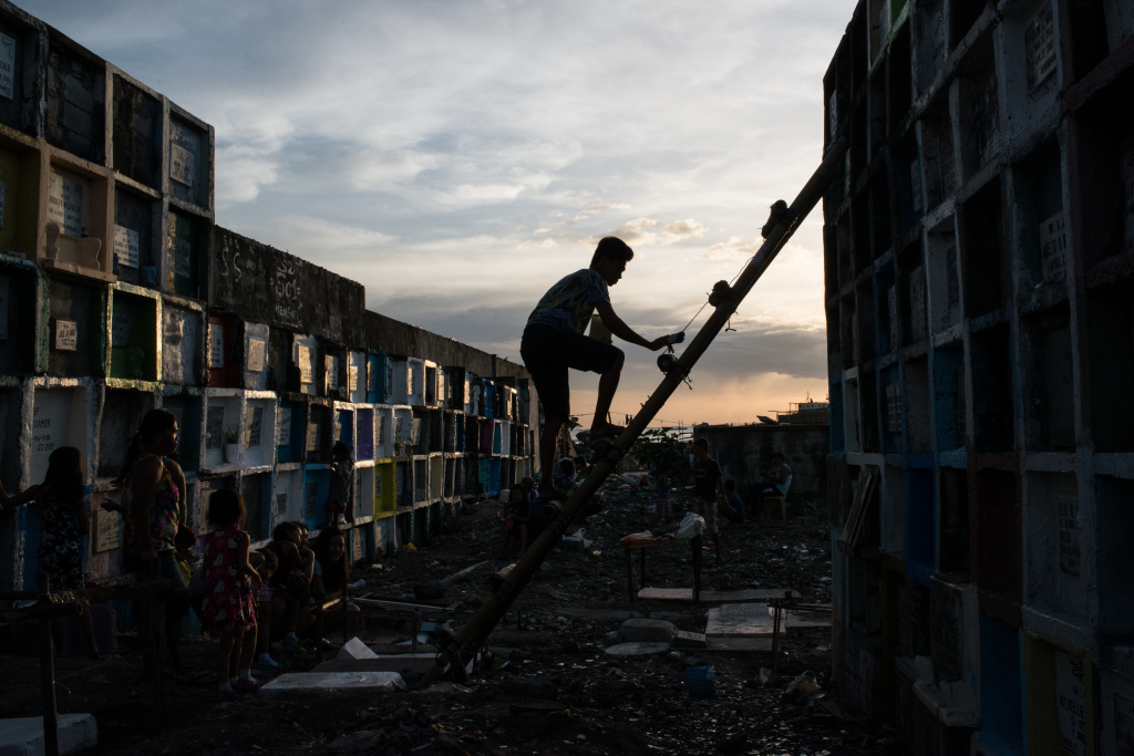 A man climbs on a ladder to reach a tombstone at a public cemetery on November 1, 2016 in Manila, Philippines. In the Philippines, family members clean tombs and often spend the night at the cemetery eating and celebrating with loved ones.