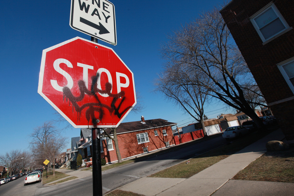 Gang graffiti is painted on a stop sign on S. Sacramento Ave. near the spot where 19-year-old Devonta Grisson was killed in a drive-by shooting on New Year's Day, 2013 in Chicago, Illinois.