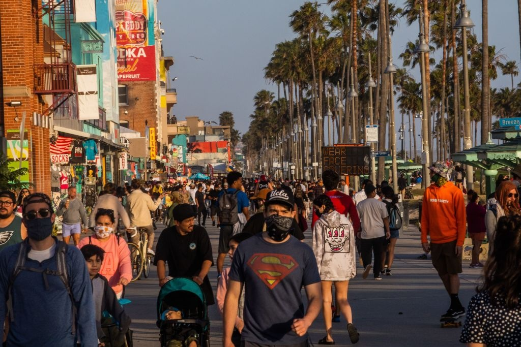 People walk at the boardwalk in Venice Beach during the first day of the Memorial Day holiday weekend amid the novel Coronavirus, COVID-19, pandemic in California on May 23, 2020.