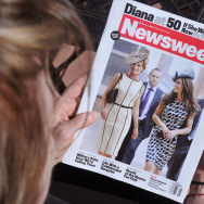 A Newsweek magazine is viewed by a reade