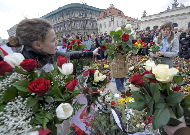 People carry flowers in front of the Presidential Palace in Warsaw on April 10, 2010, as they gather to pay tribute after the crash of the Presidential plane in Smolensk. A plane carrying Polish president Lech Kaczynski and much of the country's military and state elite crashed in thick fog in Russia on Saturday killing all 96 people on board in a blazing inferno.