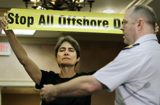An unidentified protester is removed from the room after holding up a sign during a hearing by the Coast Guard and the Interior Department's Minerals Management Service on May 11, 2010.