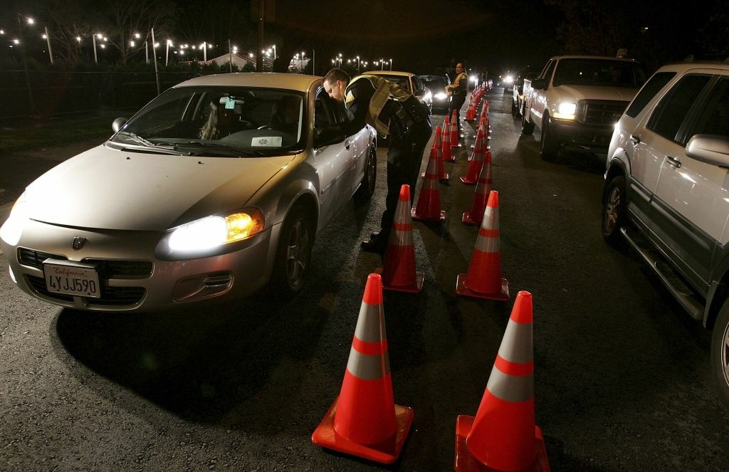 San Bruno police officers stop cars at a DUI checkpoint in San Bruno, California.