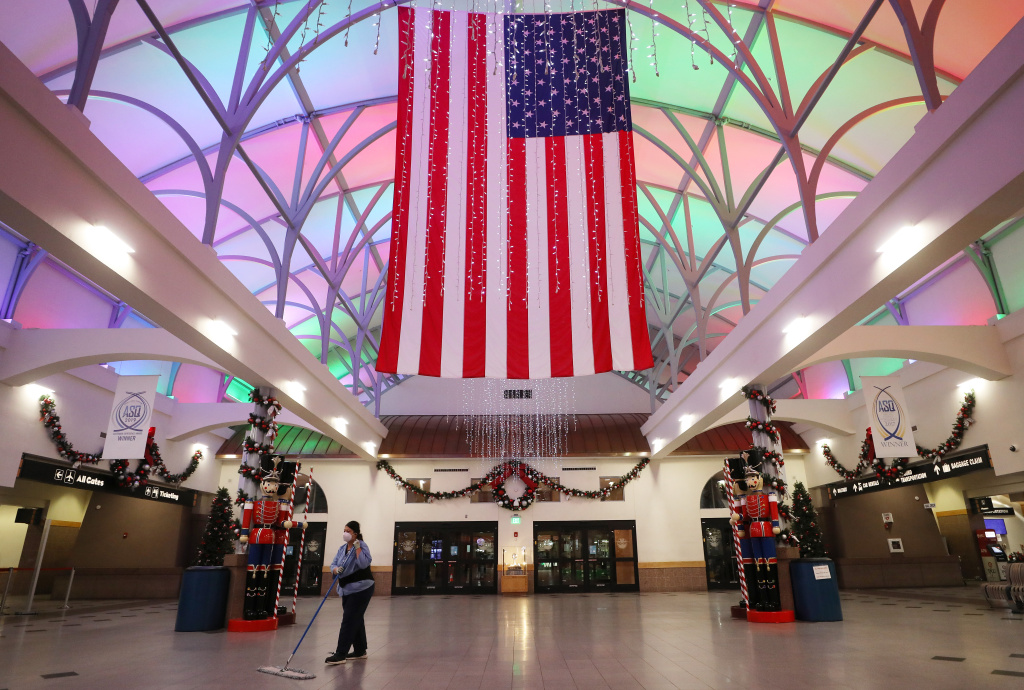 A worker cleans near an American flag and Christmas decorations in the mostly empty El Paso International Airport amid a surge of COVID-19 cases on November 12, 2020 in El Paso, Texas.