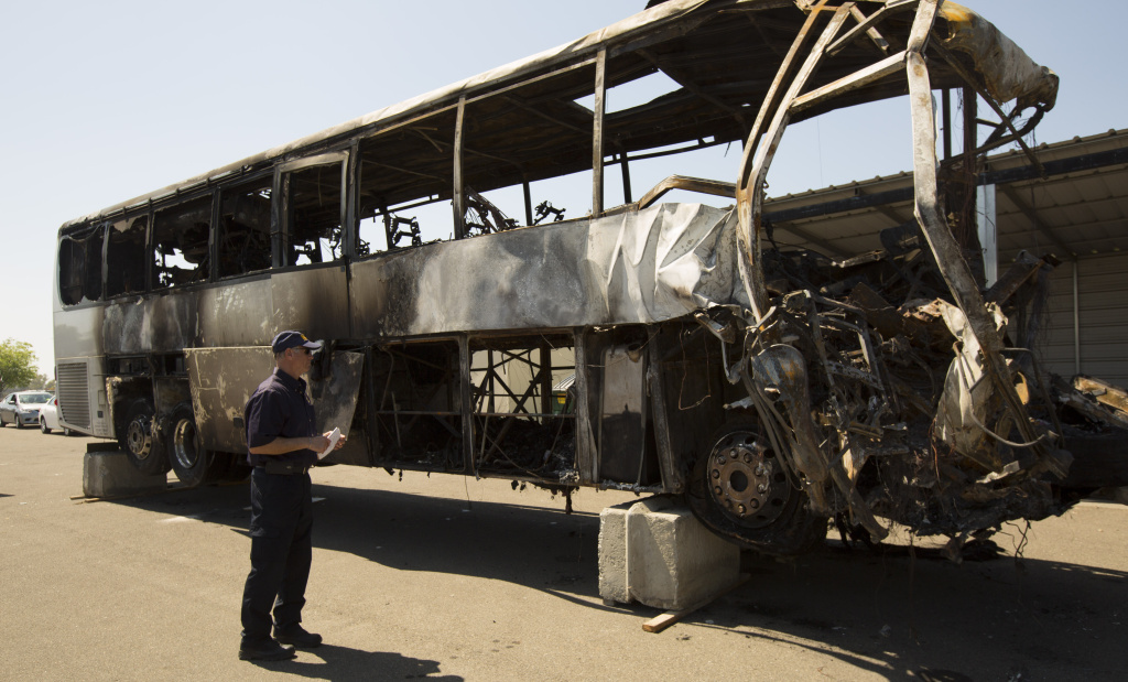 NTSB investigator Robert Accetta documents the damaged motor coach.