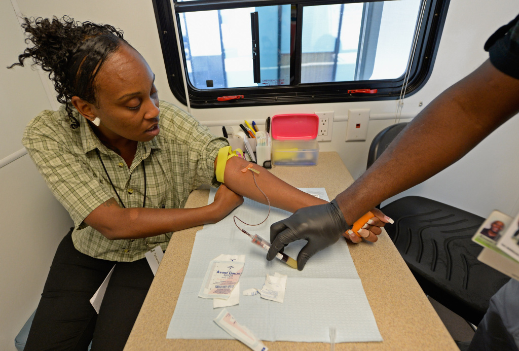 Tyshuanna Johnson get her blood drawn for HIV/AIDS and STD testing by Ernest Johnson of John Wesley Community Health Institute in one of their mobile unit during a health fair in Los Angeles, California.
