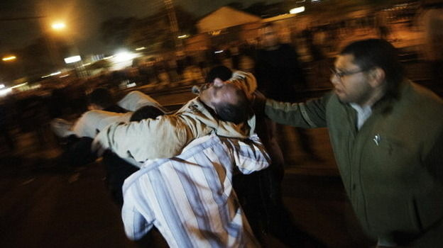 A man is carried away after being injured during overnight clashes in Cairo over President Mohammed Morsi's moves to consolidate power.