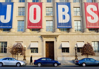 A pedestrian passes under a large banner reading 'JOBS' outside of the Chamber of Commerce January 23, 2011 in Washington, DC. Jobs and job creation are expected to be the centerpiece of US President Barack Obama's State of the Union address on January 25.