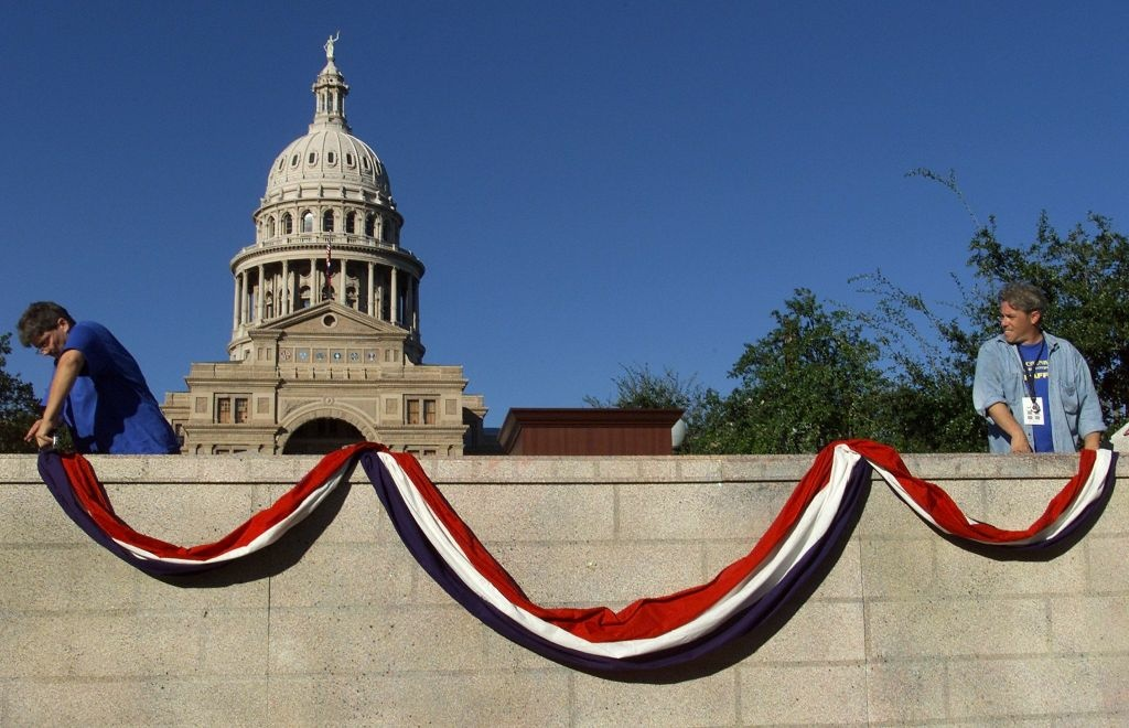 Production crew workers hang red, white and blue bunting on the stage with the Texas Capitol Building in the background.