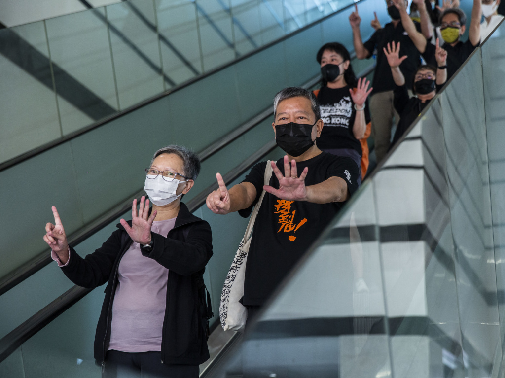Former lawmaker Cyd Ho (left) and pro-democracy activist Lee Cheuk-yan (center) gesture a protest slogan,