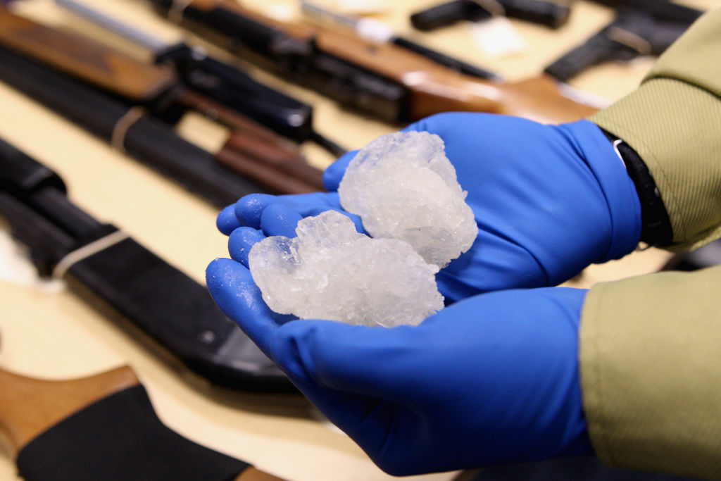 File: Detective Paul Baker holds two rocks of crystal meth with a street value of NZD$83,000 alongside firearms that were confiscated as part of Operation Slab at the North Shore Policing Centre on August 19, 2010 in Auckland, New Zealand.