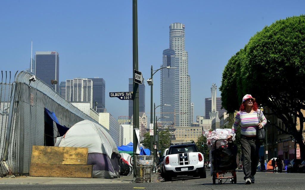 A woman pushes her cart full of belongings along the street past tents on the sidewalk near Skid Row in downtown Los Angeles, California on June 20, 2017.