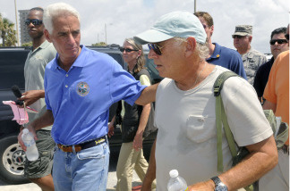 Florida Gov. Charlie Crist (left) and entertainer Jimmy Buffett walk along Pensacola Beach, where Buffett plans to open a new hotel.