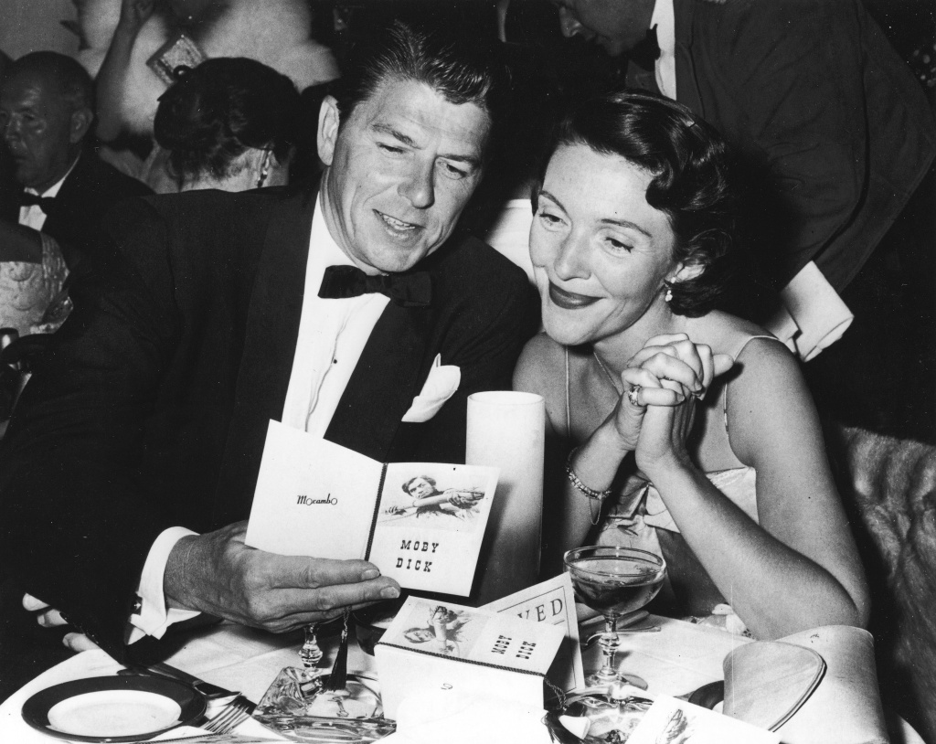 Actor Ronald Reagan and his wife, Nancy, sit at a restaurant table, looking at a brochure at the premiere party for the film 'Moby Dick,' directed by John Huston, 1956.