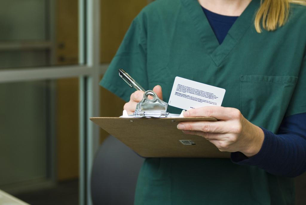 A doctor fills out patient paperwork.