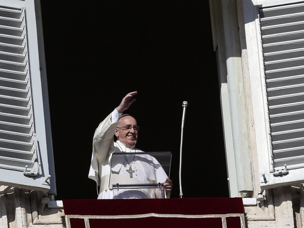 Pope Francis waves from the window of his rooms at the Vatican to faithful at St. Peter's Square at his Sunday Angelus prayer at the Vatican City on Sunday.
