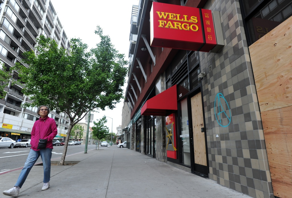 A woman walks by a damaged Wells Fargo branch in downtown Oakland, California.