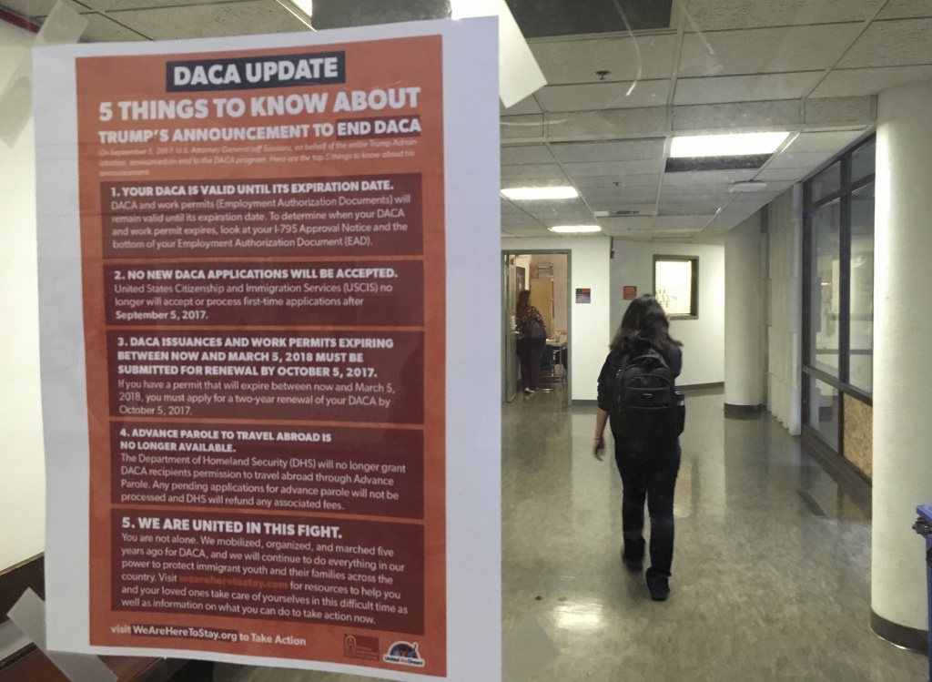 File: In this photo taken Sept. 7, 2017, a student walks past a tip sheet for Deferred Action for Childhood Arrivals recipients who fear deportation that is taped to a window on the University of California, Berkeley campus in Berkeley, Calif.
