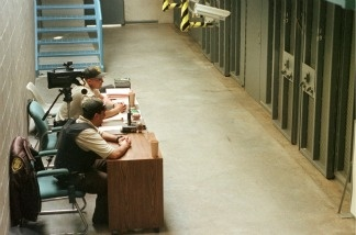 Correctional officers sit outside Karl LaGrand's No. 19 observation cell inside the Special Management Unit.