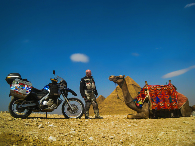 At the Great Pyramids of Giza south of Cairo, Allan Karl contemplates whether he might be better served on a camel than an motorcycle while traveling in the Sahara.
