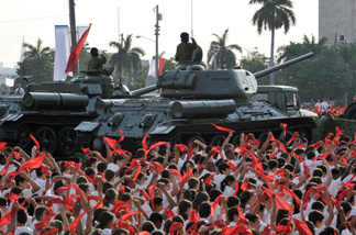 Cuban pioneers wave their kerchiefs simulating waves, on April 16, 2011, around the vintage URSS-made T-34/85 tank (R) and the SU-100 self-propelled-gun used by former Cuban President Fidel Castro in the Bay of Pigs battle, during the parade at Revolution Square in Havana to commemorate the 50th anniversary of the Bay of Pigs victory and the beginning of the Cuban Communist Party 60th Congress.