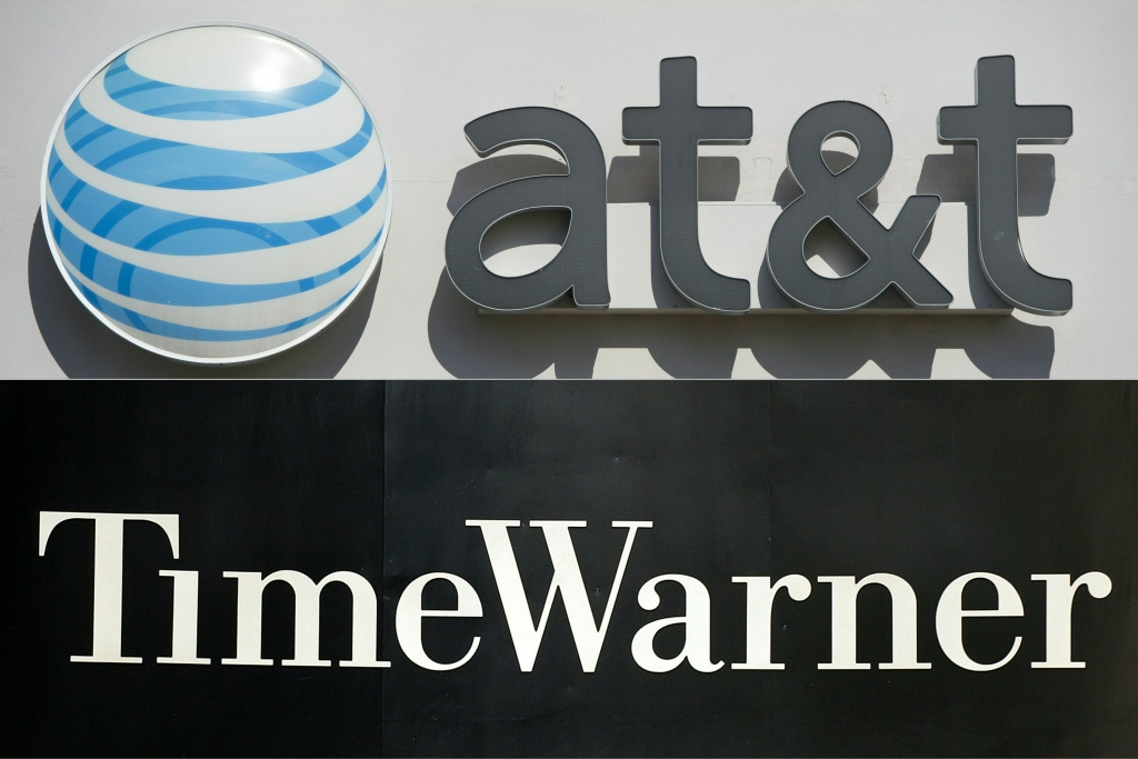 This combination of pictures created on October 21, 2016 shows an AT&T cellphone store (TOP) in Springfield, Virginia, on October 23, 2014, and the Time Warner company logo on the front of the headquarters building, 24 November, 2003 in New York.