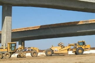 Some graders pictured near a freeway, used for construction.