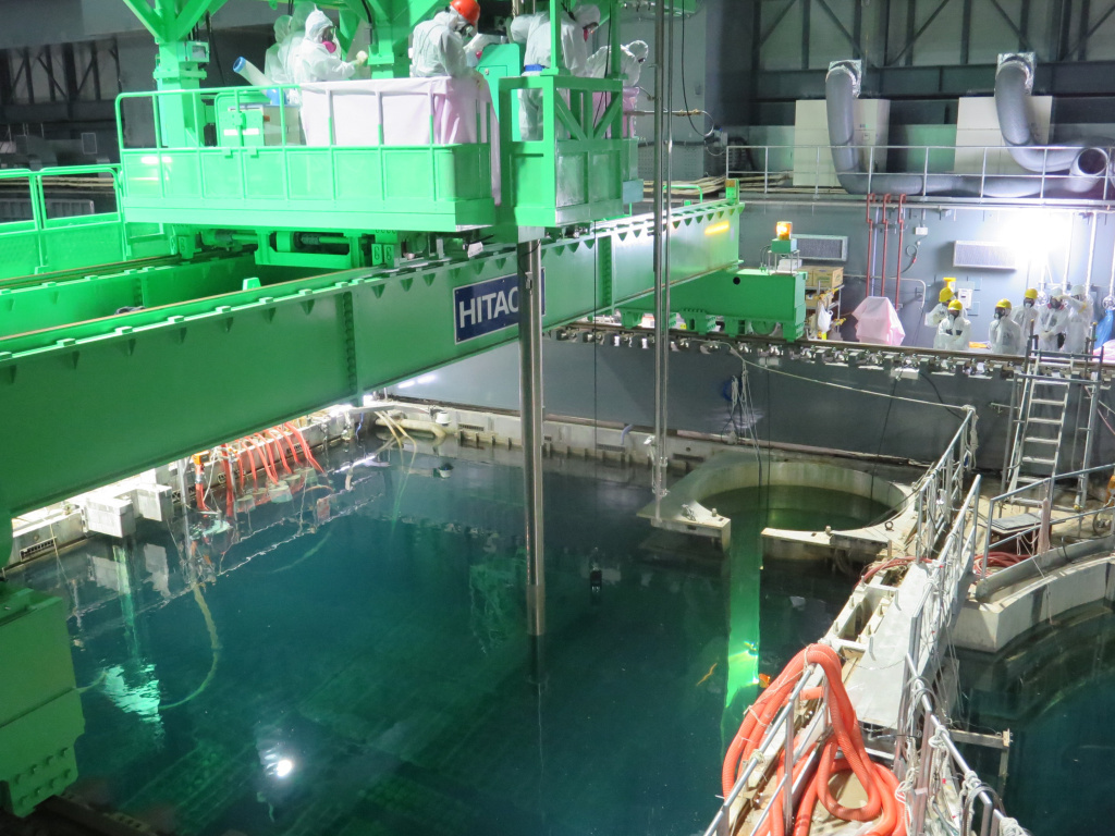 In this handout image provided by Tokyo Electric Power Co, workers remove nuclear fuel rods from a pool at No. 4 reactor of the Fukushima Daiichi Nuclear Power Plant on Monday.