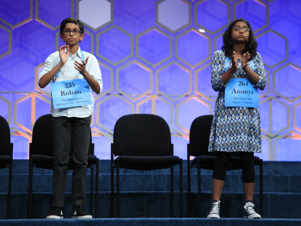 The final two spellers — Rohan Rajeev, 14, from Edmond, Okla., and Ananya Vinay, 12, from Fresno, Calif., right — applaud Thursday night during the finals of the 90th Scripps National Spelling Bee, in Oxon Hill, Md.