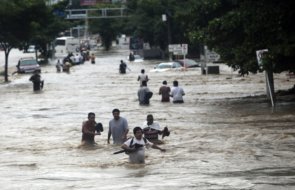 Residents attempt to flee from the flooded area in Acapulco, Guerrero state, Mexico, after heavy rains hit the area on Sept. 16, 2013.
