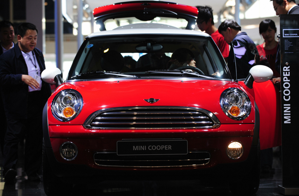 A four cylinder Chili Red Mini Cooper attracts attention among crowds gathered at the Beijing Auto Show on April 21, 2008.
