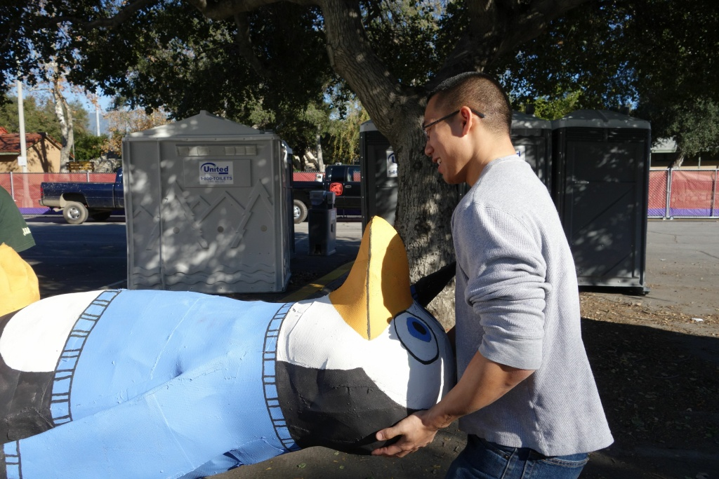 Cal Poly Pomona student Nelson Chang unloads one of a dozen steel and foam penguin sculptures that will be covered with California-grown flowers and displayed on the university's Rose Parade float.