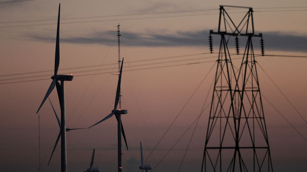 Wind turbines stand alongside an electrical tower at the National Wind Technology Center, run by the U.S. Department of Energy, outside Boulder, Colo.
