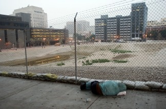 A homeless man sleeps on the sidewalk next to a prepared downtown lot where the new Los Angeles United States Courthouse was supposed to be built.