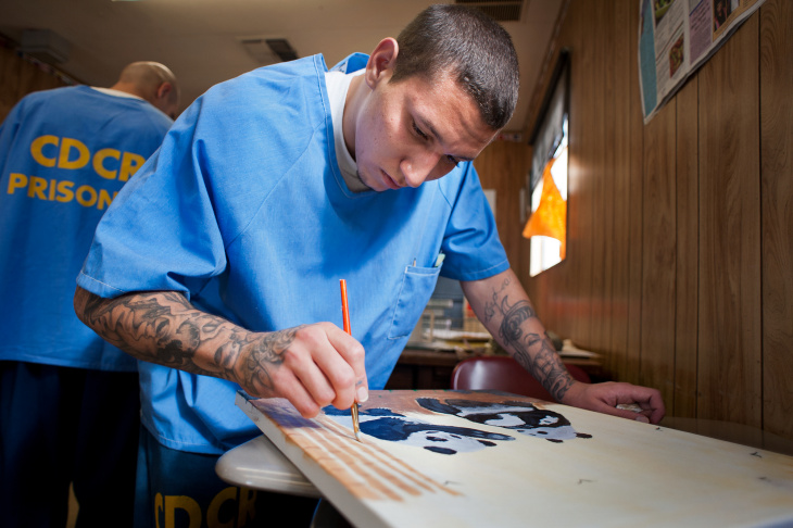 Inmate Rudy Sigala paints pandas for his three children. The class is Sigala's first time painting, but he has drawn before.