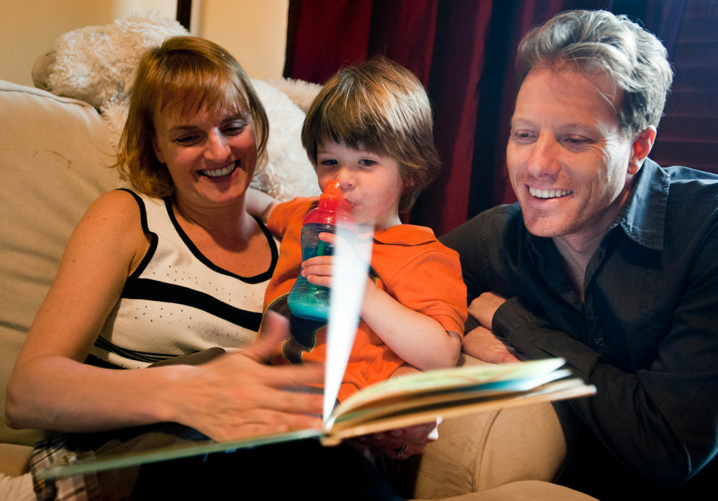 Kacy and Jack Andrews read a book before nap time to their 3-year-old adopted son Sawyer in their Glendale home. Californians adopt more children than in any other state.