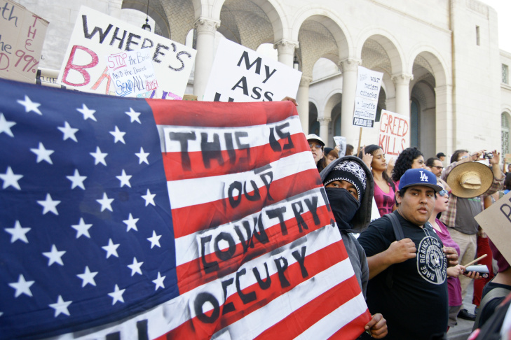 Protesters hold signs after a march to Los Angeles City Hall during the