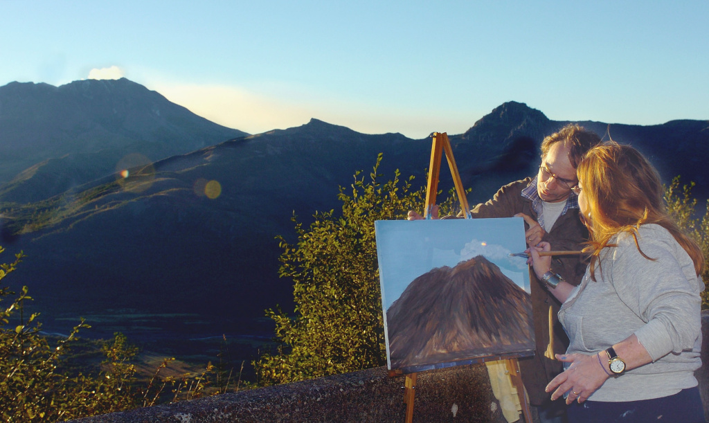 Teri Dewey, right, assisted by her husband, Joe Dewey, adds a steam plume to her painting of Mount St. Helens, after setting up her easel at Elk Creek Overlook in Washington on October 14, 2004.